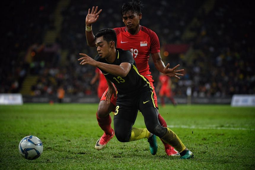 Muhammad Amiruldin Bin Muhammad Nodin of Singapore in action against Muhammad Ariff Farhan Bin MD Isa of Malaysia during the SEA Games Football match held at Shah Alam Stadium on Aug 16, 2017.