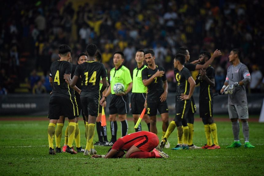 Relief on the faces of the Malaysians as a Singapore player slumps to the ground.