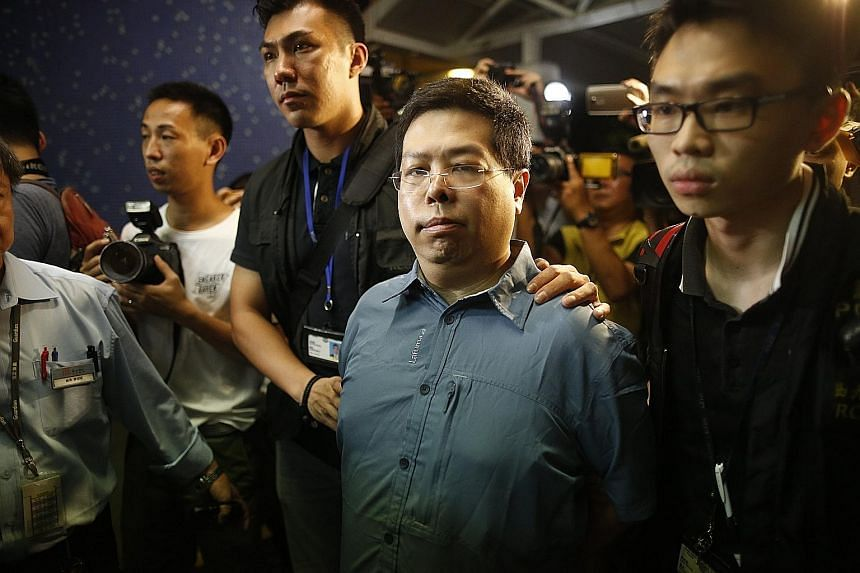 Opposition member Howard Lam was taken away by police in a van, in handcuffs on Monday morning. In a press conference last week, Lam displayed his stapled thighs.