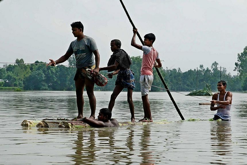 Bangladeshis moving about on a raft made of banana tree trunks yesterday in an area submerged by flood in Kurigram, northern Bangladesh. Floods in northern Bangladesh have killed at least 27 people in the last few days and affected more than 500,000,