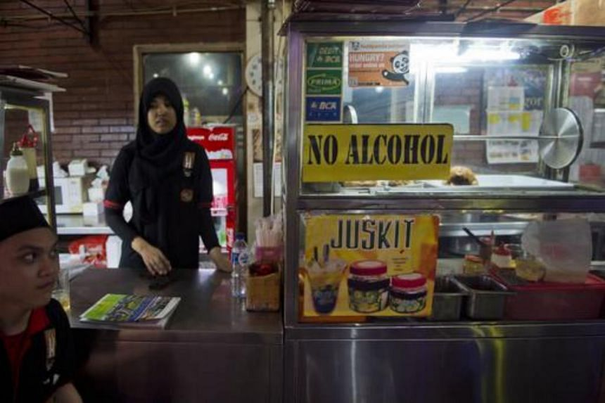 A restaurant worker waits for customers as a 'no alcohol sign' is displayed on the food stall in a tourist district in Jakarta.