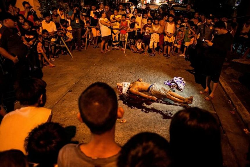 This file photo taken on August 2, 2017 shows residents looking at the body of an alleged drug user killed by unidentified assailants in Manila.