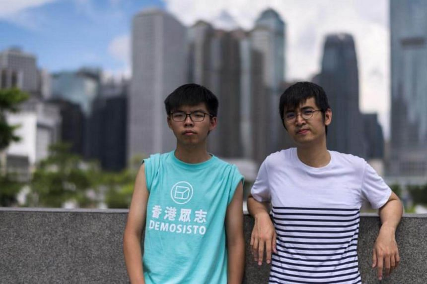 Joshua Wong (left) and Alex Chow, leaders of Hong Kong's 'Umbrella Movement', pose after an interview with AFP in Hong Kong on August 16, 2017.