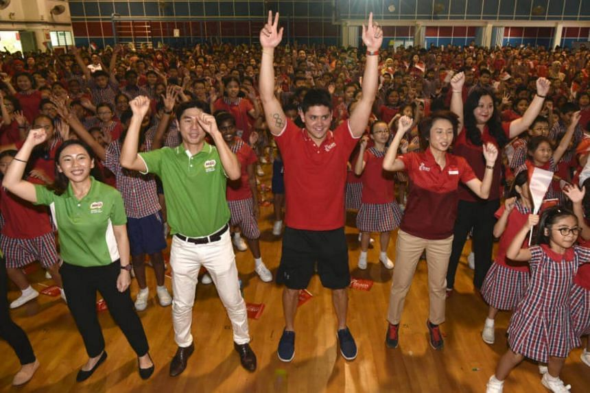 Olympic champion Joseph Schooling is swarmed by excited students during his visit to Yuhua Primary School.