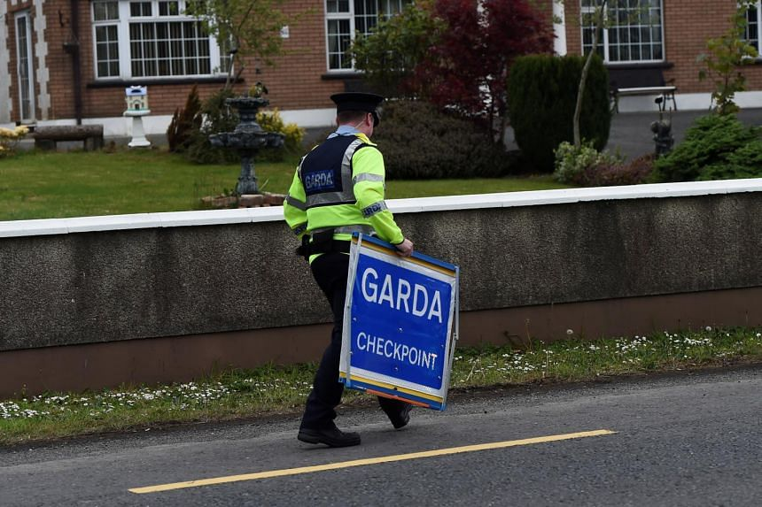An Irish police officer removes a Garda checkpoint sign at the Armagh and County Louth border between Northern Ireland and Ireland, during a visit by European Union Chief Negotiator for Brexit Michel Barnier, on May 12, 2017.