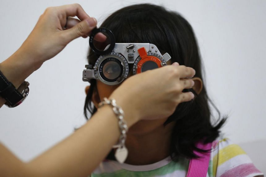 A girl getting her eyes checked for myopia during a charity drive in Plaza Singapura.