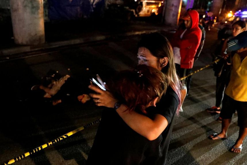 A woman weeps near the body of a man who police said was killed in a spate of drug related violence in Manila, Philippines, on Aug 16, 2017.