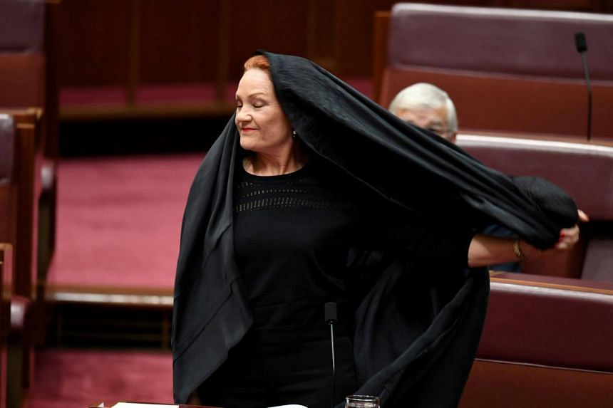 Australian One Nation party leader, Senator Pauline Hanson pulls off a burqa in the Senate chamber at Parliament House in Canberra, Australia, on Aug 17, 2017.