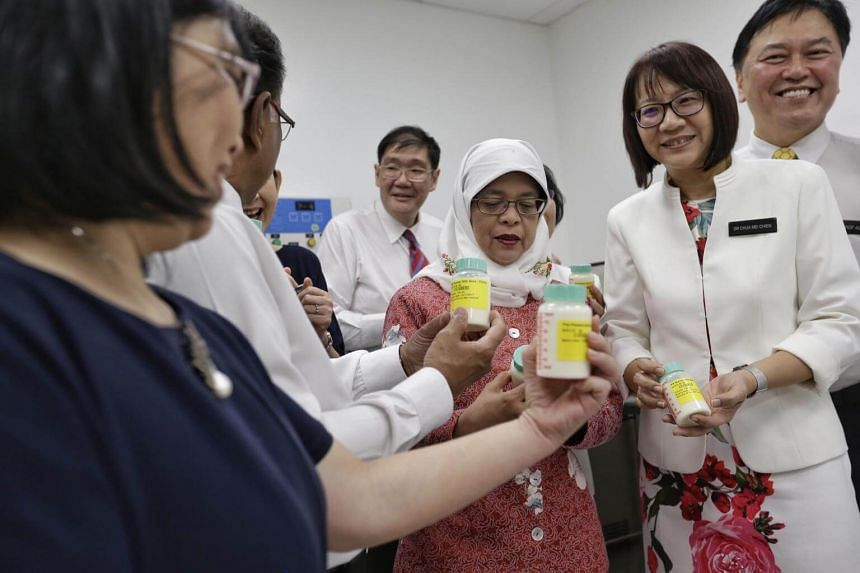 Madam Halimah Yacob and guests looking at bottles of human milk at the milk bank at KK Women's and Children's Hospital on Aug 17, 2017.