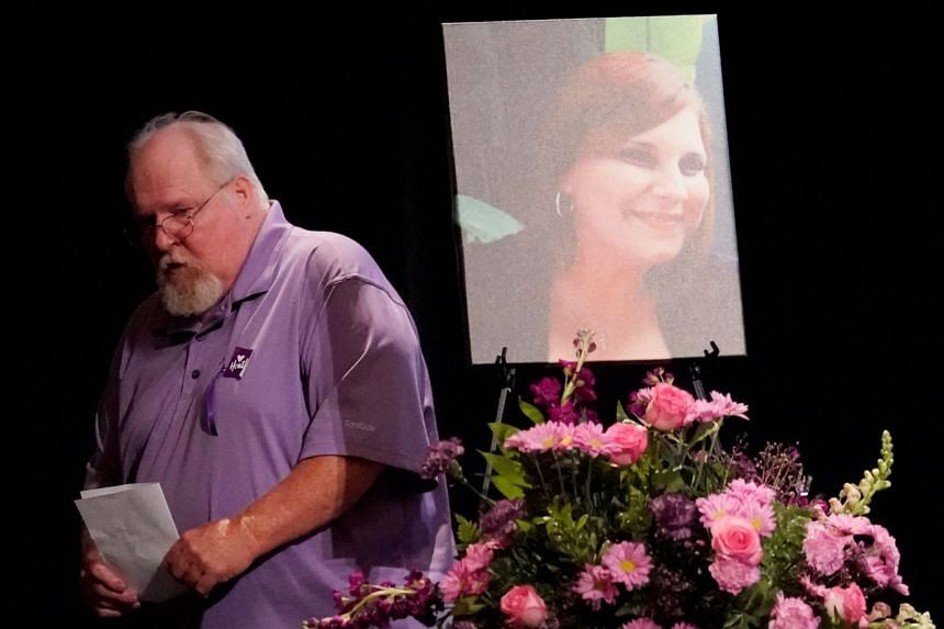 Heather Heyer's father, Mark Heyer, passes a picture of his daughter after speaking at her memorial service.