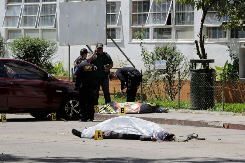 Police officers stand next to two bodies after suspected gang members attacked a hospital in Guatemala City.
