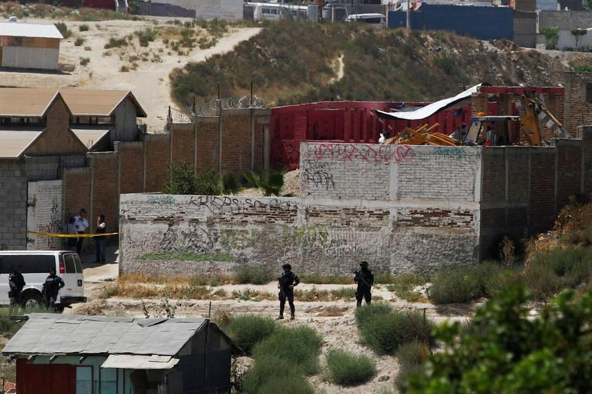 Policemen stand guard as forensic investigators work on the exhumation of a mass grave at a plot of land that is believed to have been used to bury unidentified victims of drug violence, in Tijuana, Mexico, on Aug 16, 2017.