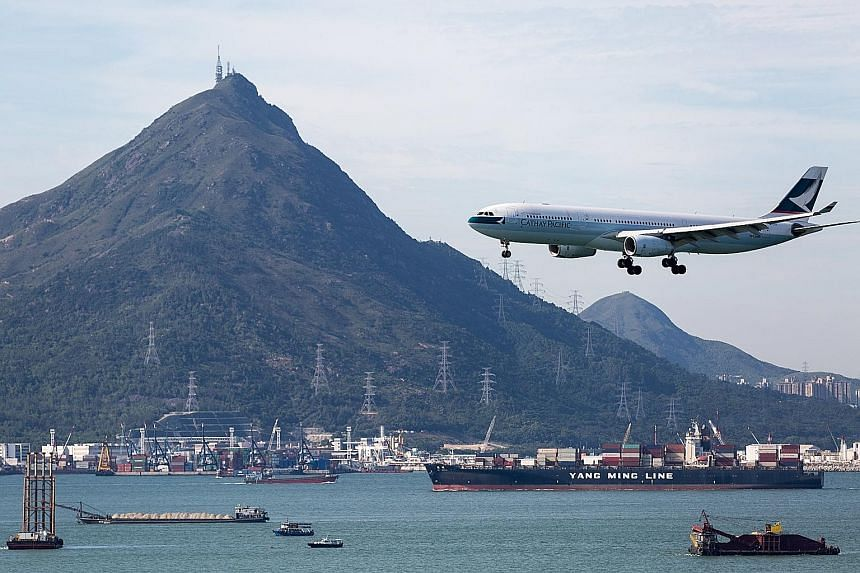 A Cathay Pacific Airways jetliner preparing to land at Hong Kong's airport on Tuesday. The airline is on track for its first ever back-to-back annual loss since it was founded in 1946.