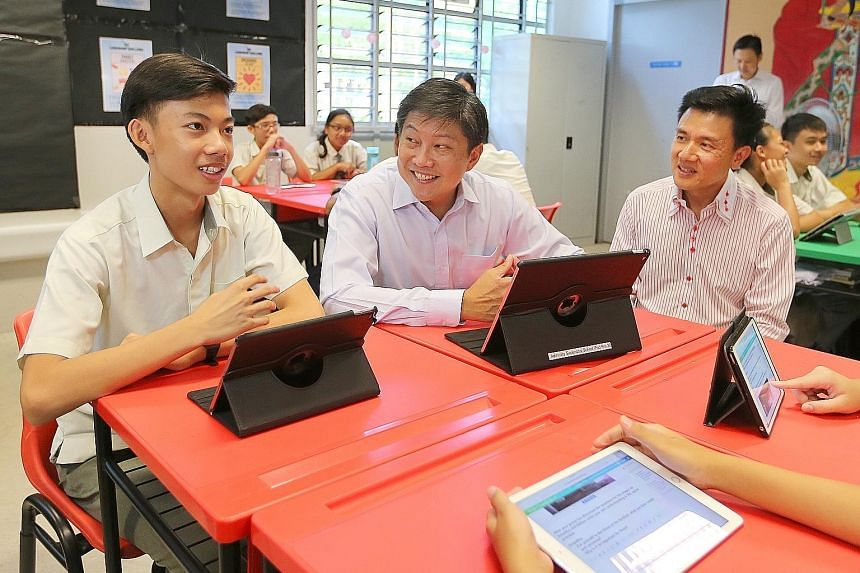 Education Minister (Schools) Ng Chee Meng (centre) checking out the use of the Singapore Student Learning Space with Secondary 3 student Jannsen Low Yu Heng and classmates at Admiralty Secondary School yesterday, accompanied by the principal Toh Thia