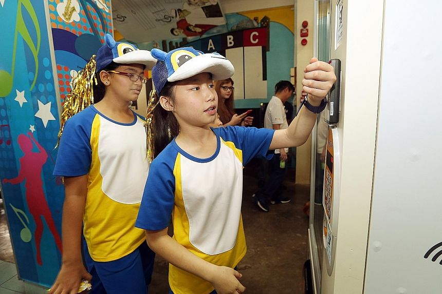 Pupil Vernice Lim, 11, using her smartwatch at a vending machine to pay for a drink at Admiralty Primary yesterday.