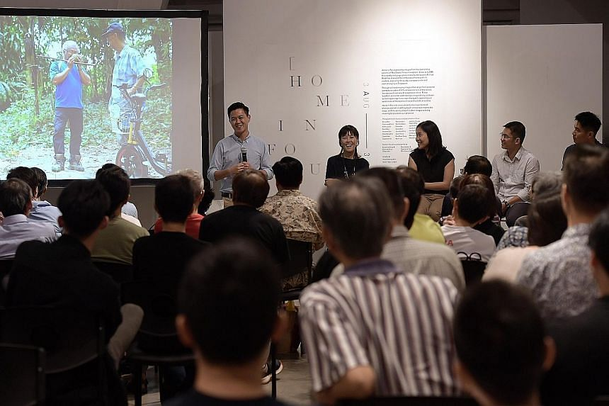 Former ST photojournalist Desmond Lim speaking about his picture spread Durian Hunters at the Home In Focus photo exhibition yesterday. Seated next to him are (from left) Objectifs centre director Emmeline Yong and ST photojournalists Neo Xiaobin, Se