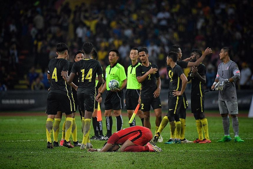 Singapore's Under-22 footballer Amiruldin Asraf slumped over in despair after hosts Malaysia came from behind to grab a 2-1 SEA Games group-stage win at the Shah Alam Stadium in Kuala Lumpur last night. It was the Young Lions' second straight loss at