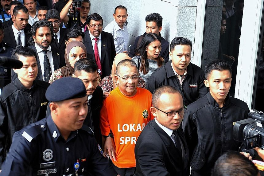 Mohd Isa Samad (in orange), who was appointed Felda chief in 2011 but replaced in January this year, arriving at the Putrajaya court complex yesterday for his remand hearing. The probe allegedly involved the land agency overpaying by hundreds of mill