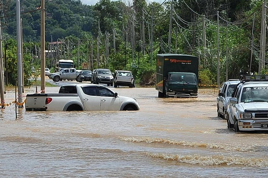 Vehicles on a flooded road in Kota Kinabalu, Sabah, on Tuesday. Heavy rain has hit several states in Malaysia, closing schools, cutting off remote villages and forcing hundreds of people to be evacuated from their homes. Sabah was the worst affected,