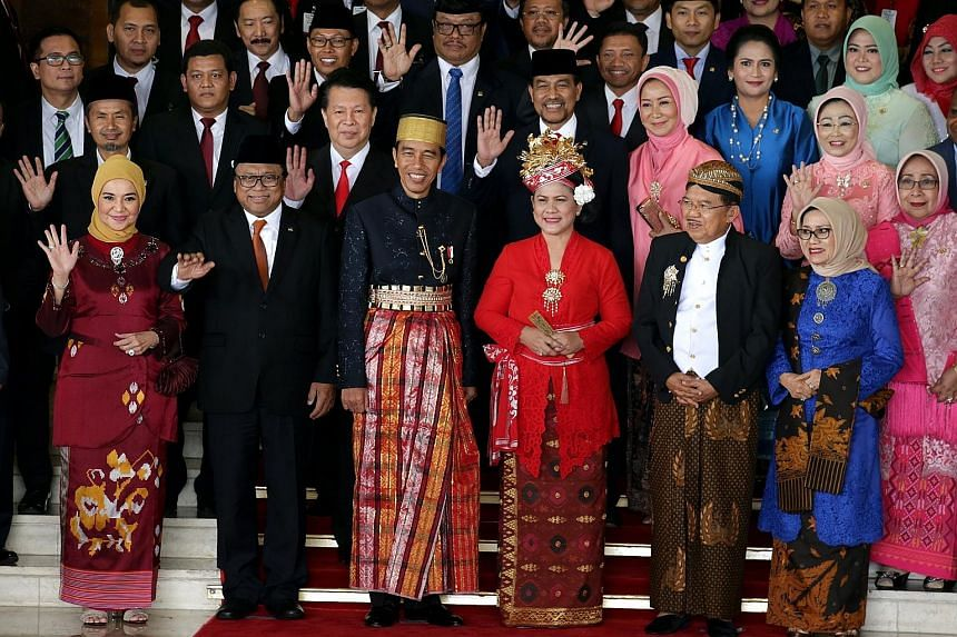 Indonesian President Joko Widodo and his wife, Iriana (centre), wearing traditional Bugis attire, together with Vice-President Jusuf Kalla and his wife, Mufidah (right), and lawmakers after Mr Joko delivered his annual address at the Parliament build