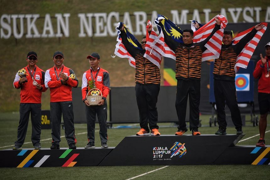 Singaporean archers (from left) Pang Toh Jin, Alan Lee and Ang Han Teng stand on the podium with their silver medals after the SEA Games compound men's team event on Aug 17, 2017.
