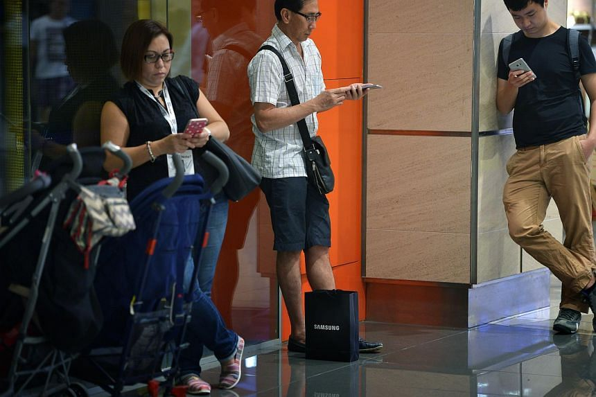People looking at their mobile phones at Suntec City.