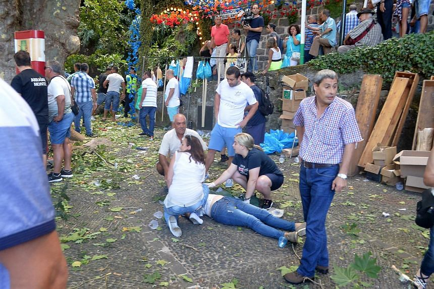 Some people help injured persons on the ground after a tree had fallen in Funchal on Aug 15, 2017.