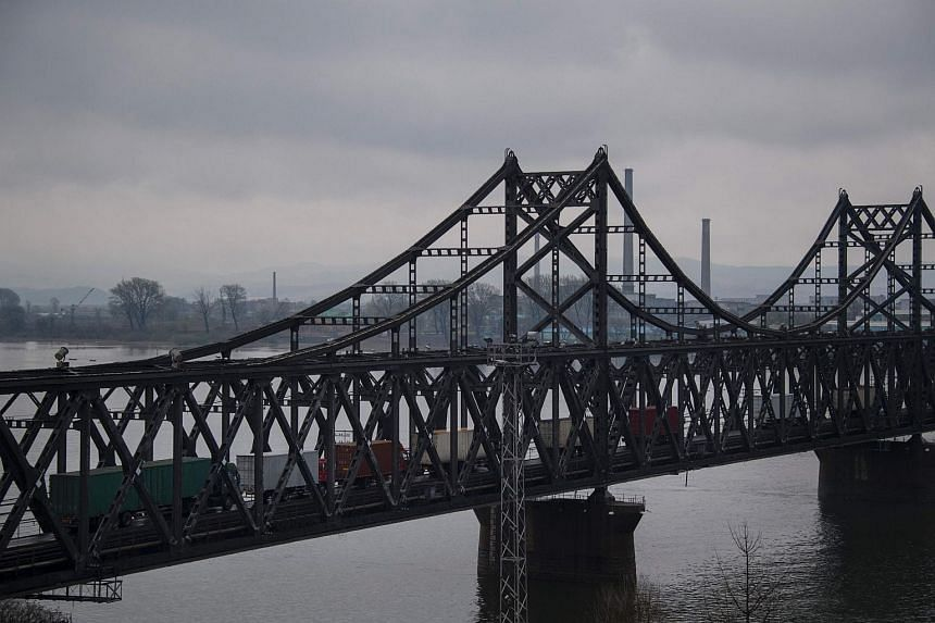 Trucks crossing the Friendship Bridge from the Chinese border city of Dandong to North Korea's Sinuiju over the Yalu river.