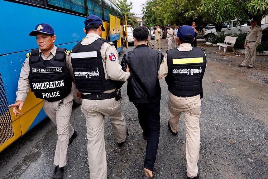 Chinese nationals suspected of telecom fraud are escorted into a bus to an airport in Preah Sihanouk province, awaiting deportation to China, in Phnom Penh, Cambodia.