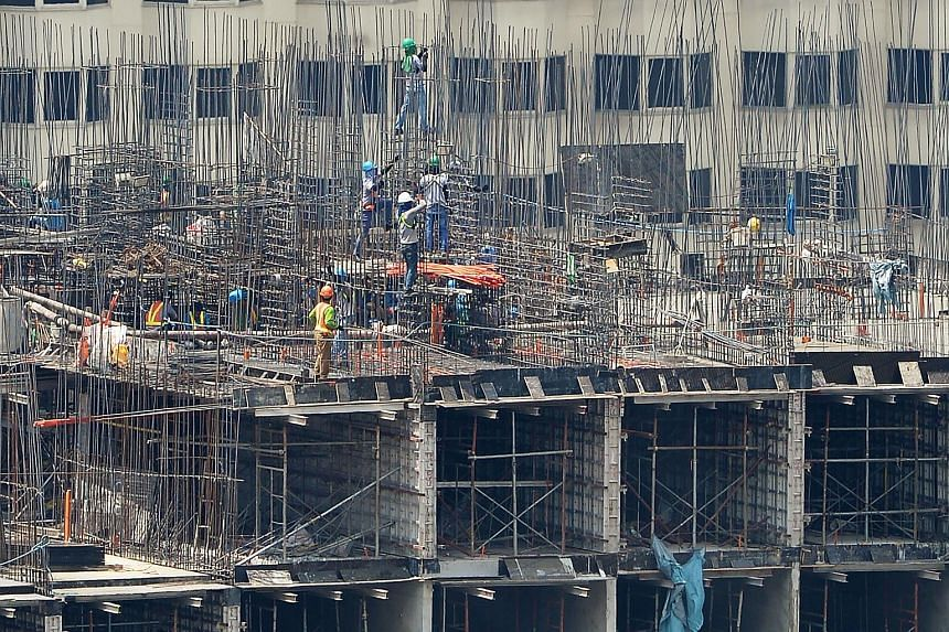 Workers stand on steel bars as they work at a construction site in Manila.