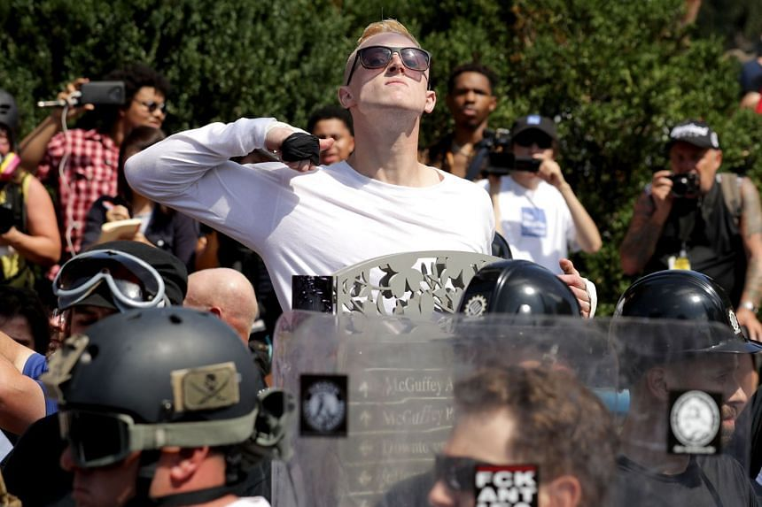 A man makes a slashing motion across his throat towards counter-protesters at a far-right rally in Charlottesville, Virginia.
