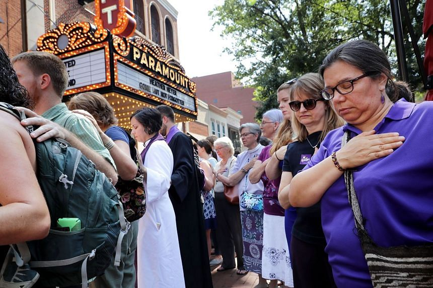 People observe a moment of silence during the memorial service for Heather Heyer outside the Paramount Theatre.