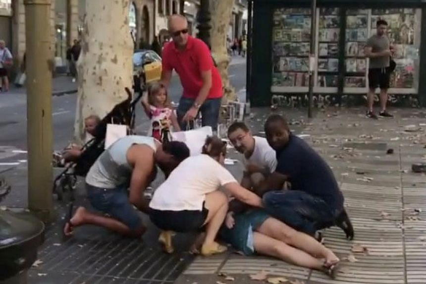 People help an injured woman lying on the ground.