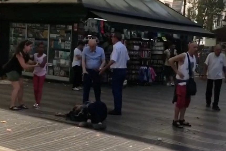 People help an injured person lying on the ground.