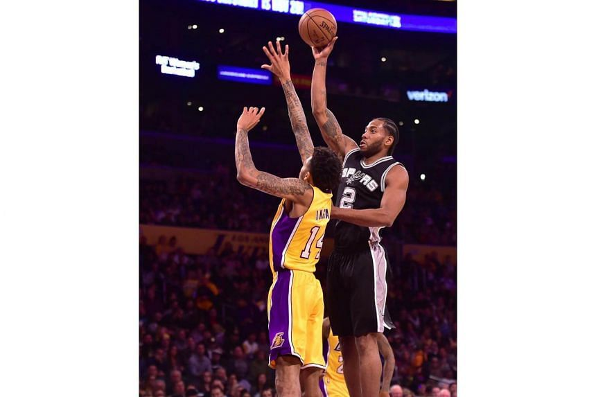 Kawhi Leonard (right) of the San Antonio Spurs shooting under pressure from Brandon Ingram of the Los Angeles Lakers during the NBA basketball matchup in Los Angeles, California, on Nov 18, 2016.