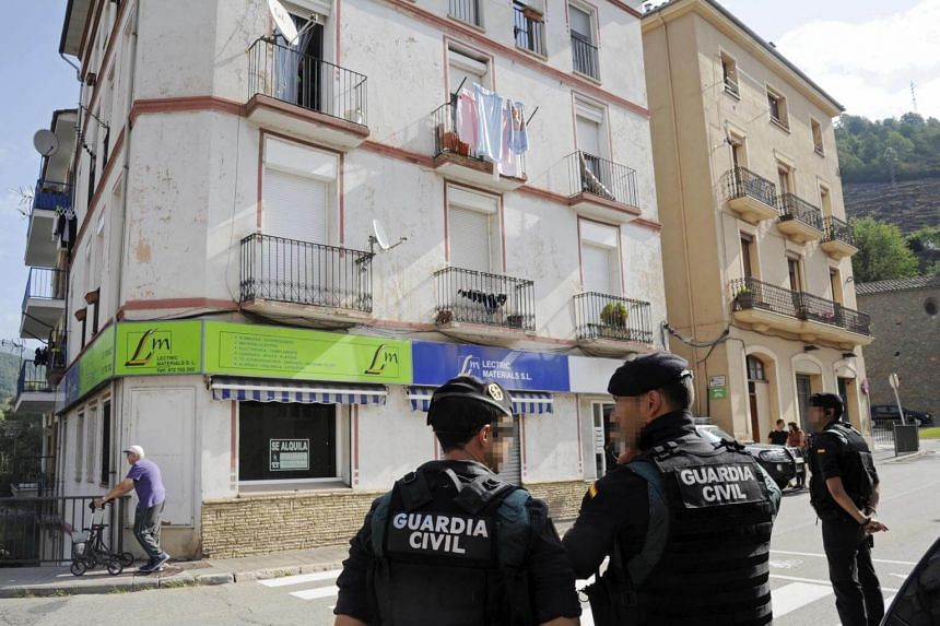 Spanish security forces members stand guard outside an apartment building during a raid in the town of Ripoll, Catalonia, on Aug 18, 2017.