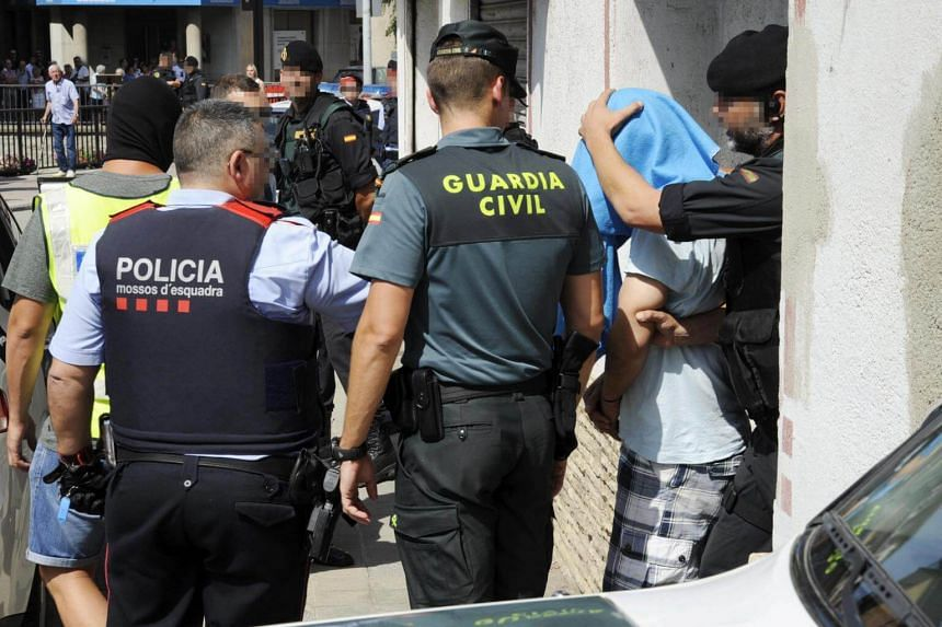 Spanish security forces escort a defendant (2nd from right) after he was arrested during a raid in the town of Ripoll, Catalonia, on Aug 18, 2017.