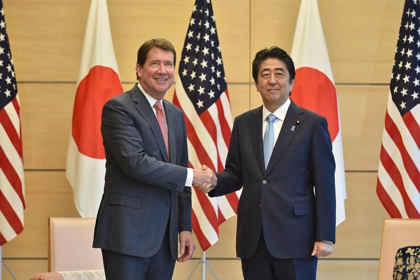 New US Ambassador to Japan William Hagerty (left) shakes hands with Japan's Prime Minister Shinzo Abe (right) at Abe's official residence in Tokyo, Japan, on Aug 18, 2017.