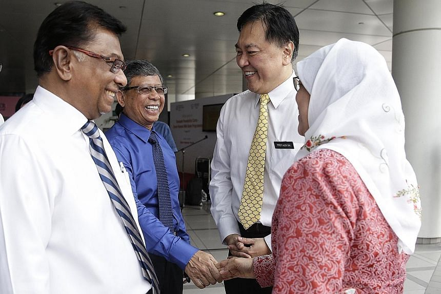 Madam Halimah Yacob and Mr Mohamed Salleh Marican exchanging a handshake at the launch of Singapore's first milk bank yesterday. With them are Temasek Foundation Cares chairman Richard Magnus (far left) and KKH chief executive Alex Sia.