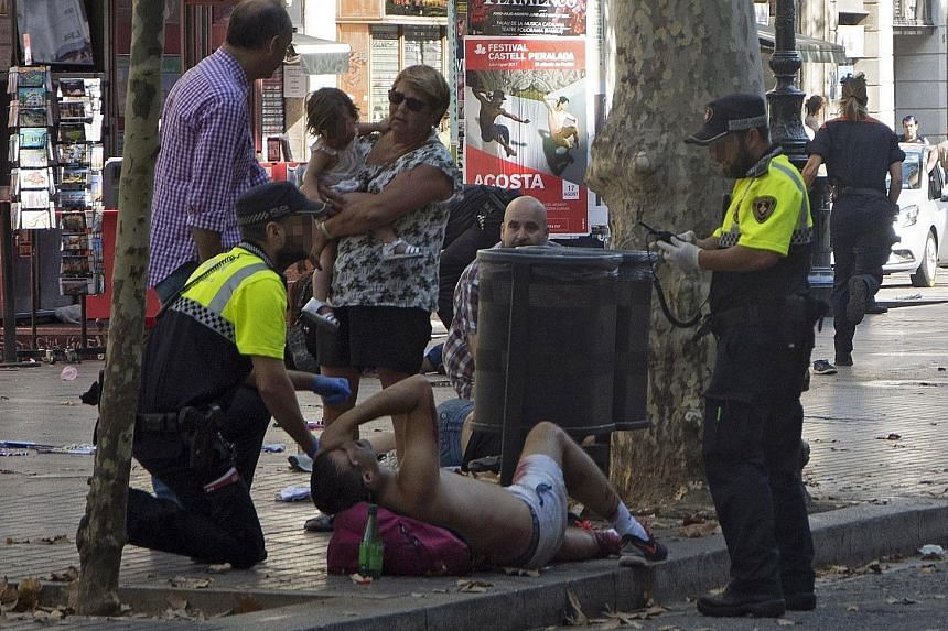 The aftermath after the van crashed into pedestrians in the popular tourist area of Las Ramblas in Barcelona yesterday. At least one person died in the incident, which Barcelona police said was a terrorist attack. Police officers attending to one of