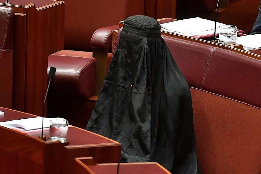 One Nation party leader Pauline Hanson wearing a burqa to the Senate (top) in Canberra yesterday, before she pulls it off (above) after 20 minutes to highlight what she said were the security issues it posed, linking it to terrorism as fellow senator