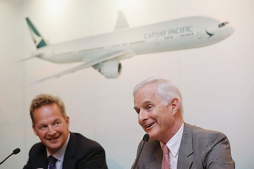 Cathay Pacific's chairman John Slosar (right) and CEO Rupert Hogg at a conference in Hong Kong on Wednesday. The airline reported a net loss of HK$2.05 billion (S$360 million) for the six months to June.