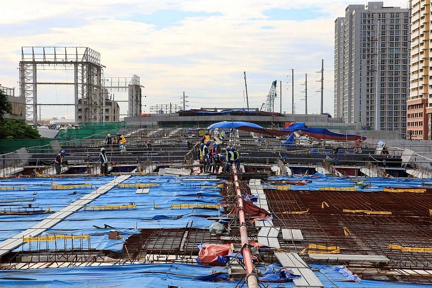 Workers laying out steel bars during the construction of an 8km, four-lane elevated highway in Makati City, metro Manila, on Aug 3. A rebound in government spending and the farming sector helped boost the Philippines' economic growth.