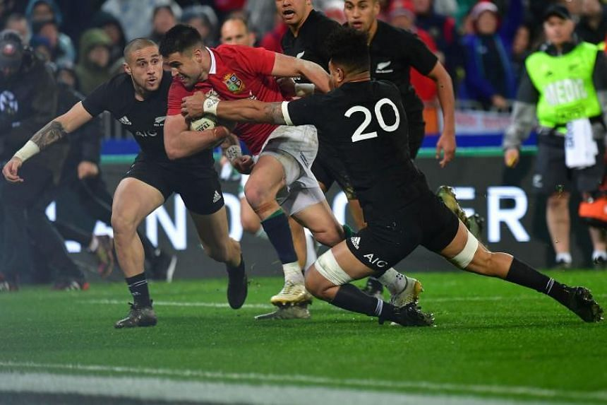 British and Irish Lions' Conor Murray (centre) scores a try as New Zealand All Blacks' T.J. Perenara (left) and Ardie Savea (jersey No. 20) attempt to tackle him during the match in Wellington in July 2017.