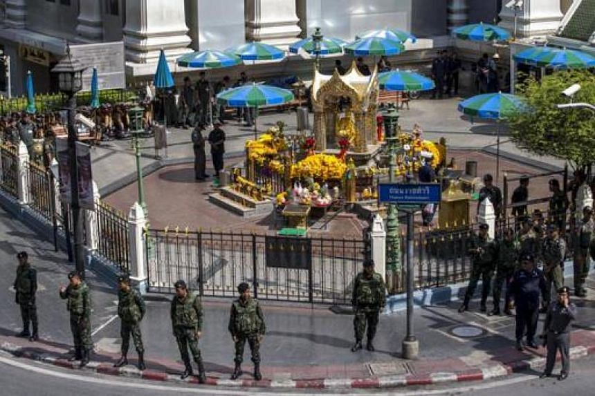 Military personnel and police officers standing guard before a crime re-enactment near the bomb site at Erawan Shrine in Bangkok on Sept 26, 2015.