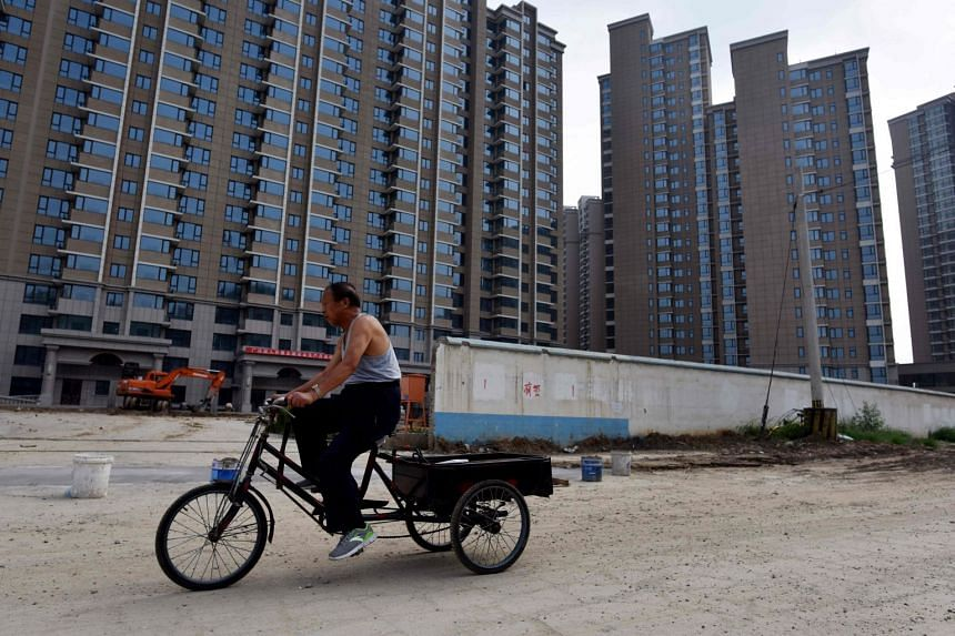 A man cycles past the construction site of a housing complex in Beijing, on Aug 15, 2017.