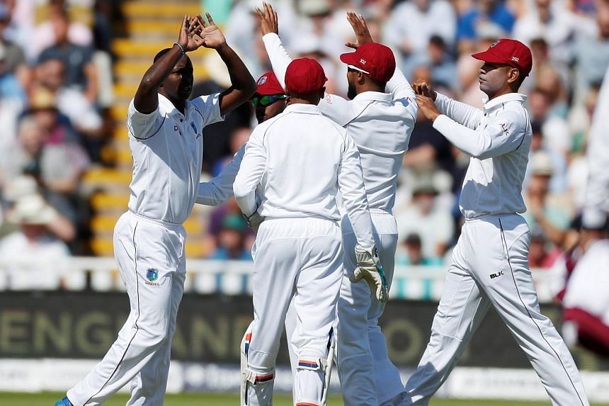 West Indies' Kemar Roach (left) celebrates taking the wicket of England's Mark Stoneman.