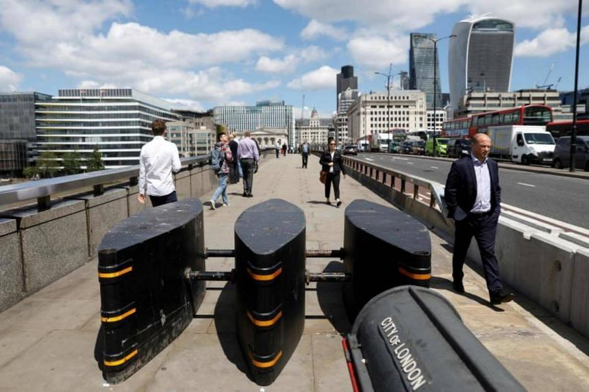 Pedestrians walking through newly installed barriers on the pavement on London Bridge in London on June 7, 2017.