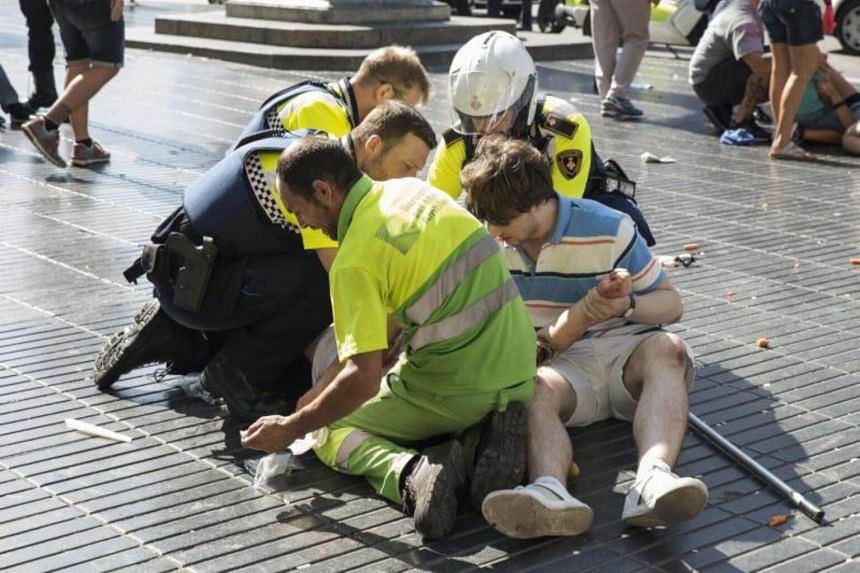 A person is helped by Spanish policemen and two men after a van ploughed into the crowd, killing at least 13 people and injuring around 100 others on the Rambla in Barcelona on Aug 17, 2017.