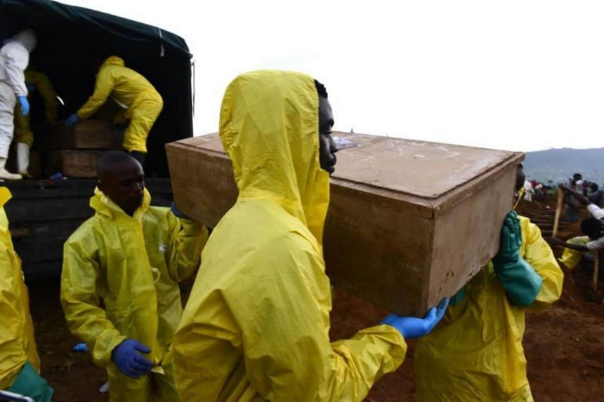 Men carry coffins of mudslide victims at the Waterloo cemetery near Freetown, Sierra Leone on Aug 17, 2017.